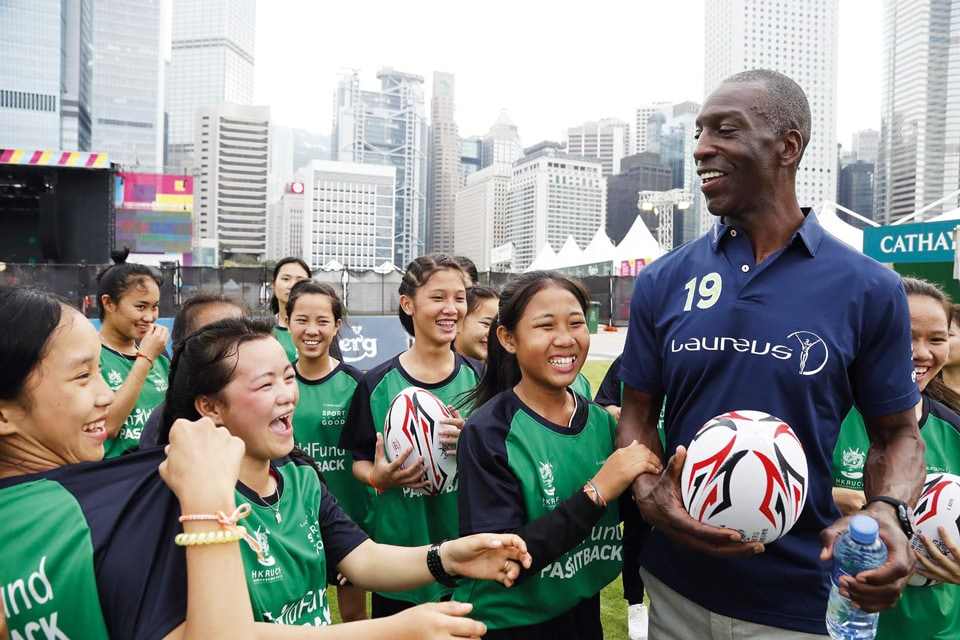 Athletic man holds rugby ball, surrounded by teenager girls in matching sports shirts